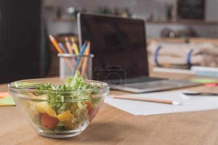 close-up shot of workplace with laptop and healthy salad