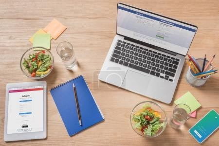 top view of workplace with digital devices and healthy salad on desk