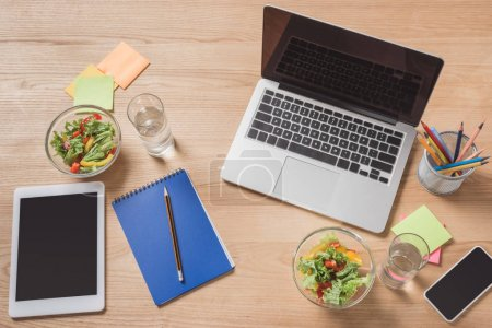 top view of workplace with digital devices and healthy salad