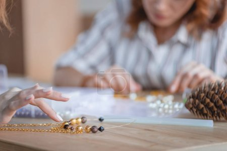 Photo for Cropped shot of women making accessories of beads in workshop - Royalty Free Image