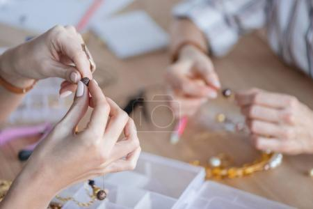 Photo for Cropped shot of women making accessories of beads at workshop - Royalty Free Image