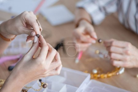 cropped shot of women making accessories of beads at workshop