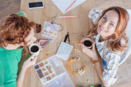 Foto de Vista de ángulo alto de mujeres jóvenes felices tomando café en el taller de accesorios hechos a mano - Imagen libre de derechos