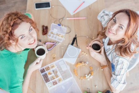 Photo for High angle view of young women drinking coffee in handmade accessories workshop - Royalty Free Image