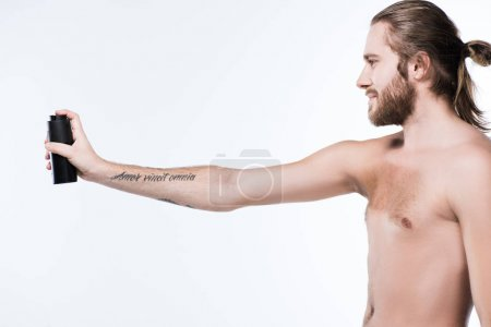 image of young smiling long haired man holding deodorant spray in outstretched hand with tattoo, isolated on white