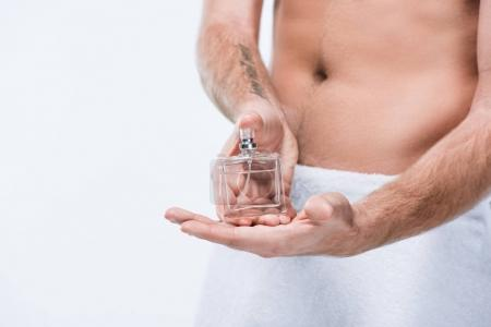 Cropped image of man with towel around waist holding glass bottle with perfume, isolated on white