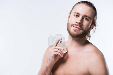 Bearded young man looking at camera while holding glass bottle with perfumes against his neck, isolated on white