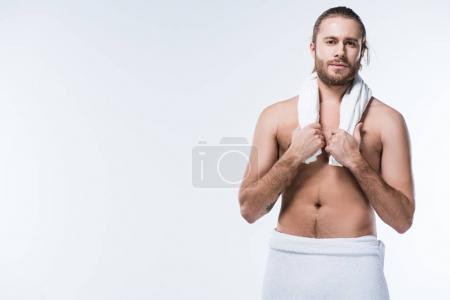 Young bearded caucasian man holding bath towel around his neck and looking at camera, isolated on white