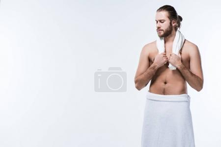 Half naked man with bath towel around his neck and waist, looking down, isolated on white