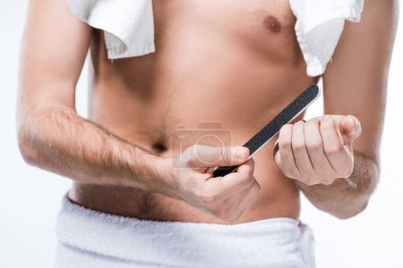 Midsection of  man with bath towel on shoulders and around waist holding nail file in hand,  isolated on white