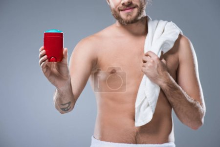Smiling half naked man holding bath towel over shoulder in one hand and deodorant stick in another, isolated on gray