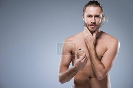 Young handsome man with beard holding glass bottle with perfumes in hand, isolated on gray