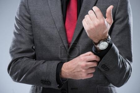 Midsection of businessman in formal suit adjusting button on sleeve, isolated on gray