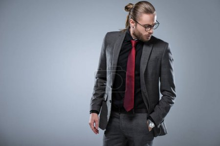 Long haired brunette businessman in glasses looking down with hand in pocket, isolated on gray