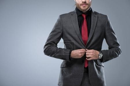 Cropped image of businessman buttoning his jacket, isolated on gray