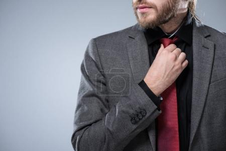 Cropped image of bearded businessman touching his red tie, isolated on gray