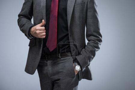 Cropped image of businessman holding side of jacket and hand in pocket, isolated on gray