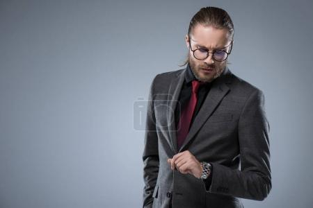 Businessman in glasses looking on his watch, isolated on gray