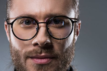 Portrait of handsome bearded man in glasses, isolated on gray