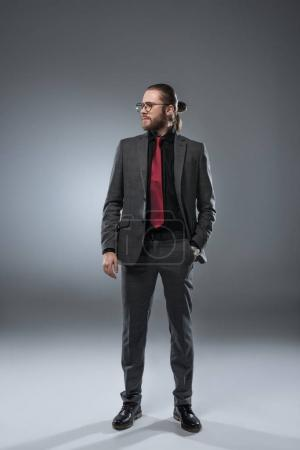 Businessman in glasses looking away with hand in pocket of jacket, isolated on gray