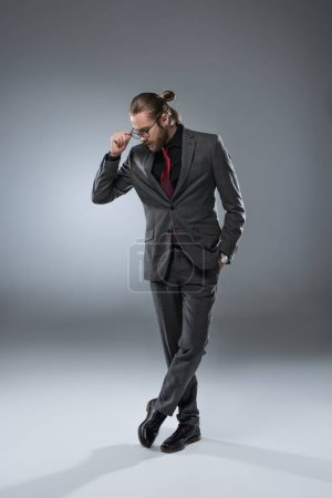 Photo for Long haired businessman in glasses looking down while standing with crossed legs, isolated on gray - Royalty Free Image
