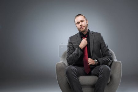 Serious businessman sitting in armchair and straightening tie, while looking at camera, isolated on gray