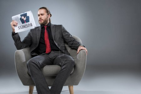 Caucasian bearded businessman sitting in armchair and reading newspaper, isolated on gray