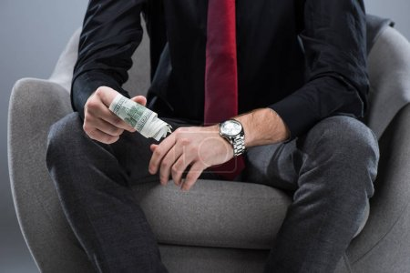 Midsection of businessman holding money in hands, while sitting on armchair, isolated on gray