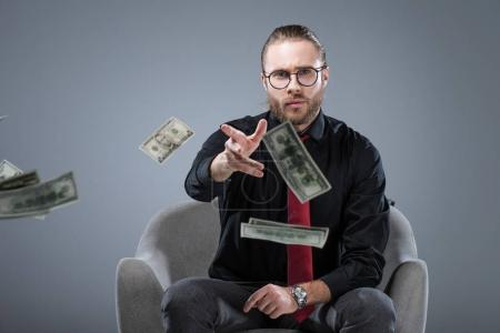 Young successful businessman in glasses sitting in armchair while throwing money to camera, isolated on gray