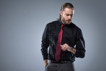 Serious man in black shirt with red tie looking on wristwatch, isolated on gray