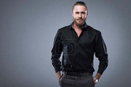 cheerful young man in black shirt with hands in pocket looking at camera, isolated on gray