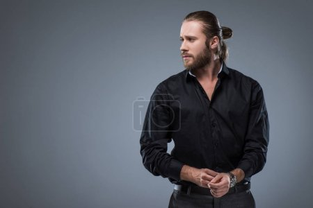 Photo for Handsome bearded man in black shirt looking away, isolated on gray - Royalty Free Image