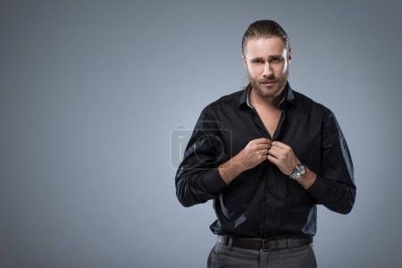 Photo pour Bel homme regardant la caméra tout en boutonnant sa chemise noire, isolé sur gris - image libre de droit