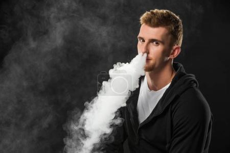 Photo pour Jeune homme barbu expirant fumée de cigarette électronique entourée de nuages de vapeur - image libre de droit