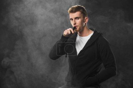 Photo pour Jeune homme barbu vapotage cigarette électronique entourée de nuages de vapeur - image libre de droit
