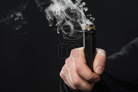 Photo for Cropped view of male hand activating electronic cigarette on black background - Royalty Free Image