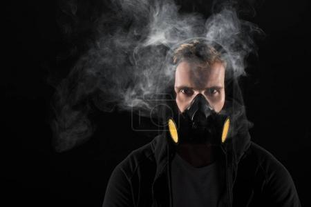 Man in black hood wearing protective filter mask surrounded by clouds of smoke