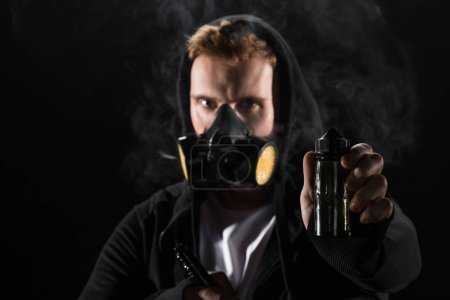 Man wearing protective filter mask smoking electronic cigarette showing E-liquid