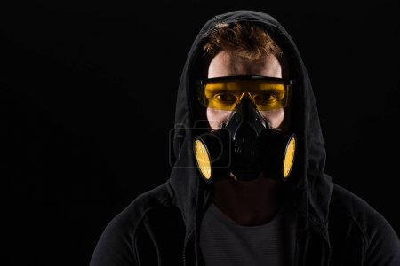 Man in black hood wearing protective glasses and filter mask isolated on black