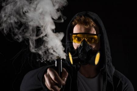 Man wearing protective filter mask activating electronic cigarette