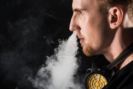 Man wearing protective filter mask exhaling smoke of electronic cigarette