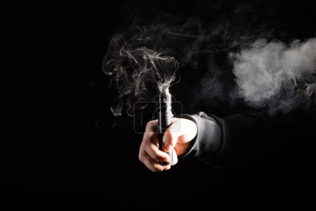 Cropped view of male hand activating electronic cigarette on black background