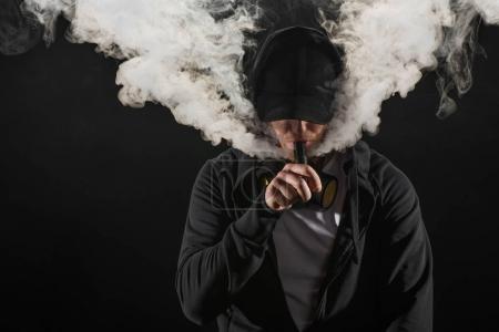 Photo pour Jeune homme barbu portant une casquette expirant fumée de cigarette électronique isolé sur noir - image libre de droit