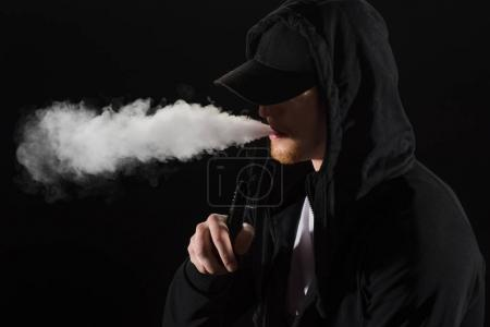 Photo for Young bearded man wearing cap exhaling smoke of electronic cigarette isolated on black - Royalty Free Image