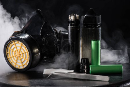 Electronic cigarette and protective filter mask with clouds of smoke on dark background