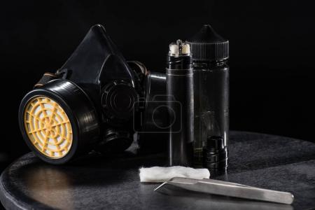 Electronic cigarette and protective filter mask isolated on black