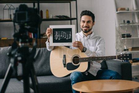 Photo pour Sourire de musique blogger affichage de notes et la guitare - image libre de droit