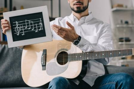 cropped image of musician holding notes and guitar