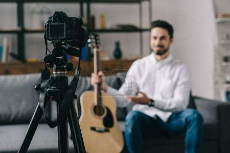 music blogger holding and describing acoustic guitar