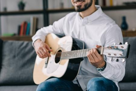 cropped image of smiling musician playing acoustic guitar